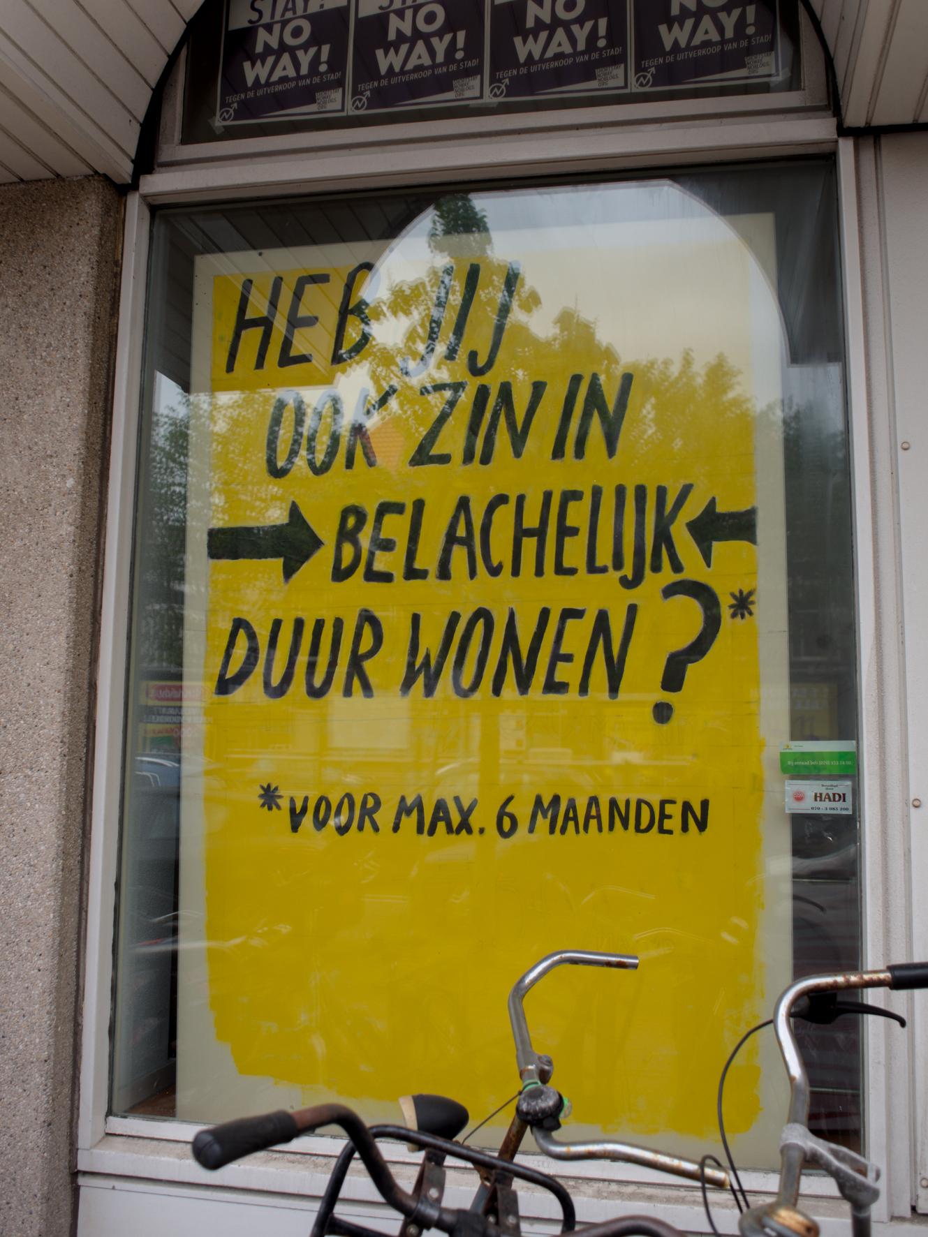 Je ziet een raam, erachter is een geel bord waar in grote letter erop staat: Heb jij ook zin in belachelijk duur wonen?* *voor max. 6 maanden?