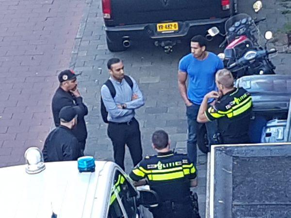 drie emensen van de kantoor RE:BORN an het praten in en circle met twee politie agenten en een ander person.linke kan zie je een politieauto.het is van boven gemaakt.