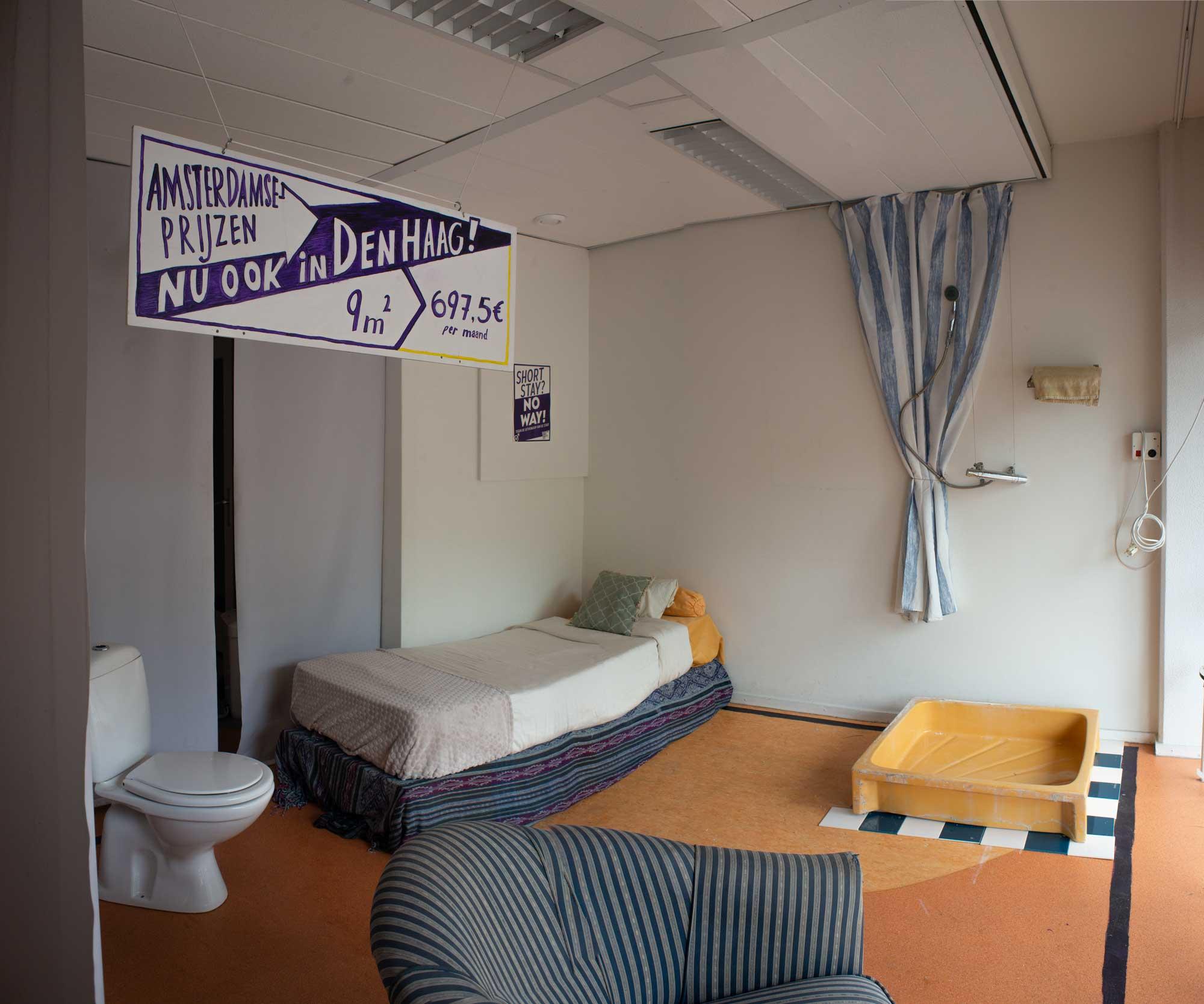 Je zeit een kamer van 3x3 vierkante meter. Links hangt een witte bord met paars letters, die zegd: Amsterdamse Prijzen - Nu ook in Den Haag! 9m2 voor 697,5€ per maand. Links staat een WC, rechts daarvan een eenpersonsbed,rechts daarvan een geel douchbak met een douchgordijn. Er is ook nog een lounge stoel. De kamer zit erg vol.